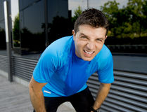 Young attractive man leaning exhausted after running session sweating taking a break to recover in urban street. Summer background Stock Photography