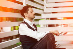 Young attractive man listening music. Handsome hipster meditates. Beautiful man relaxing outdoors while listening music. Young hipster using his smartphone for Royalty Free Stock Photography