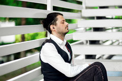 Young attractive man listening music. Handsome hipster meditates. Beautiful man relaxing outdoors while listening music. Young hipster using his smartphone for Stock Photography