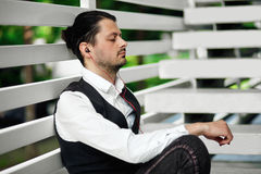 Young attractive man listening music. Handsome hipster meditates. Beautiful man relaxing outdoors while listening music. Young hipster using his smartphone for Royalty Free Stock Photos