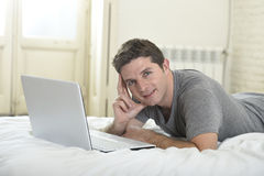 Young attractive man lying on bed or couch enjoying social networking using computer laptop at home Royalty Free Stock Image