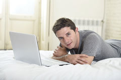 Young attractive man lying on bed or couch enjoying social networking using computer laptop at home Royalty Free Stock Images