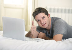 Young attractive man lying on bed or couch enjoying social networking using computer laptop at home Stock Image