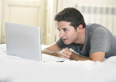 Young attractive man lying on bed or couch enjoying social networking using computer laptop at home Stock Images