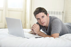 Young attractive man lying on bed or couch enjoying social networking using  computer laptop at home wireless internet Stock Photos