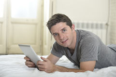 Young attractive man lying on bed or couch enjoying social networking using digital tablet computer internet at home Royalty Free Stock Image
