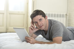 Young attractive man lying on bed or couch enjoying social networking using digital tablet computer internet at home Stock Image
