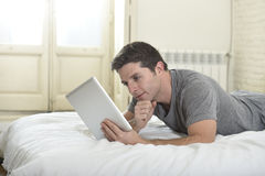 Young attractive man lying on bed or couch enjoying social networking using digital tablet computer internet at home Royalty Free Stock Photo