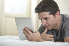 Young attractive man lying on bed or couch enjoying social networking using digital tablet computer internet at home Royalty Free Stock Photography