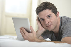 Young attractive man lying on bed or couch enjoying social networking using digital tablet computer internet at home Stock Photo