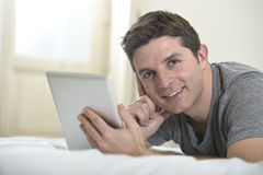 Young attractive man lying on bed or couch enjoying social networking using digital tablet computer internet at home Royalty Free Stock Images