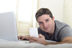 Young attractive man lying on bed or couch using mobile phone and computer laptop internet addict Stock Photo