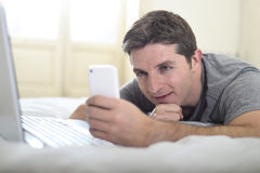 Young attractive man lying on bed or couch using mobile phone and computer laptop internet addict Royalty Free Stock Photo