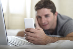 Young attractive man lying on bed or couch using mobile phone and computer laptop internet addict Stock Photography