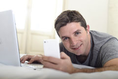 Young attractive man lying on bed or couch using mobile phone and computer laptop internet addict Royalty Free Stock Image