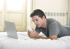 Young attractive man lying on bed or couch using mobile phone and computer laptop working from home Stock Images