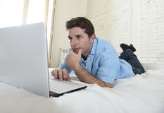 Young attractive man lying on bed enjoying social networking using computer at home Royalty Free Stock Photos