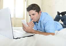 Young attractive man lying on bed using mobile phone and laptop working from home Royalty Free Stock Photography
