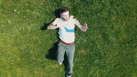 A young attractive man lying on the bright green grass and dancing stock video
