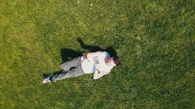 A young attractive man lying on the grass an dancing with his hands stock video