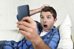 Young attractive man lying at home couch using internet on mobile phone looking surprised and shocked. Young attractive man lying at home couch using internet on stock photo