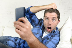 Young attractive man lying at home couch using internet on mobile phone looking surprised and shocked Royalty Free Stock Photo