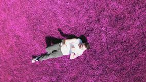 A young attractive man lying on the purple grass an dancing with his hands stock footage