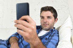 Young attractive man lying relaxed at home couch texting and surfing on internet in his mobile phone Royalty Free Stock Photography
