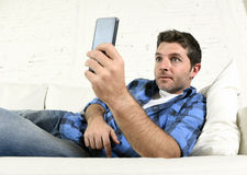 Young attractive man lying relaxed at home couch texting and surfing on internet in his mobile phone Royalty Free Stock Photos