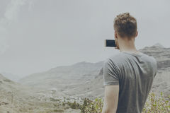Young attractive man making picture of nature landscape with his Royalty Free Stock Photo