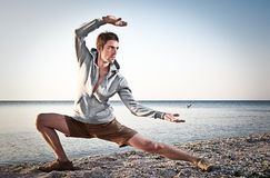 Young attractive man making Thai-chi movements Royalty Free Stock Image