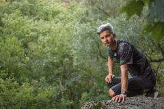 Young attractive man in nature on a boulder. In green forest Royalty Free Stock Images