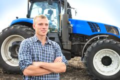 Young attractive man near a tractor. Concept of agriculture. Royalty Free Stock Photo