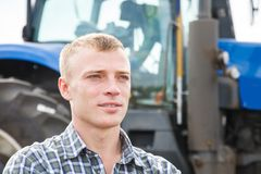 Young attractive man near a tractor. Concept of agriculture. Stock Images