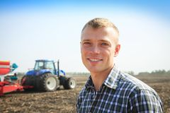 Young attractive man near a tractor. Concept of agriculture. Royalty Free Stock Photos