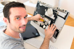 Young attractive man repairing a computer Royalty Free Stock Photography