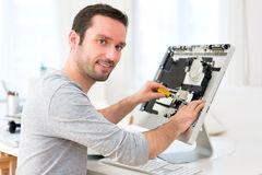 Young attractive man repairing a computer Stock Photos