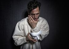Young attractive man with scars from burns, holding a white theater like mask royalty free stock image