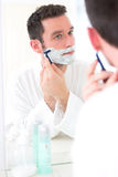 Young attractive man shaving his beard in front of a mirror Stock Photos