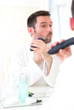 Young attractive man shaving his beard in front of a mirror. View of a Young attractive man shaving his beard in front of a mirror Royalty Free Stock Photo