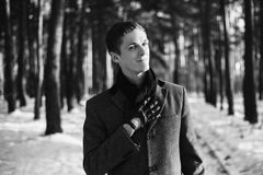 Black and white art monochrome photography. Young attractive man with short hair wearing a gray winter coat and a black scarf around his neck posing against a Royalty Free Stock Photo