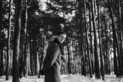 Black and white art monochrome photography. Young attractive man with short hair wearing a gray winter coat and a black scarf around his neck posing against a Royalty Free Stock Photography