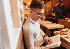 Young attractive man sitting in cafe while reading book. Stock Photography