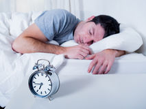 Young attractive man sleeping on bed Royalty Free Stock Images