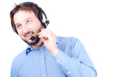 Young attractive man is speaking on microphone. And putting headphones on head Royalty Free Stock Photo