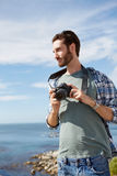 Young, attractive man standing near the ocean with digital camer Stock Photos