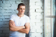 Young attractive man standing near the window and a white brick wall Stock Photography