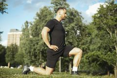 Young attractive man stretching legs outdoors doing forward lunge. Young attractive man stretching legs outdoors doing forward lunge Man is on focus and stock photo