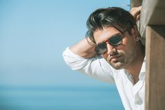 Young attractive man with sunglasses looking out over the sea during the summer. He looking forward, dressed in a white shirt and leaning on a wooden royalty free stock image
