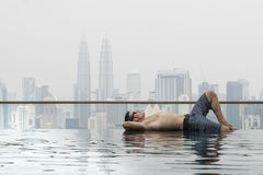 Young attractive man at the swimming pool in roof at skyscraper. Stock Photography